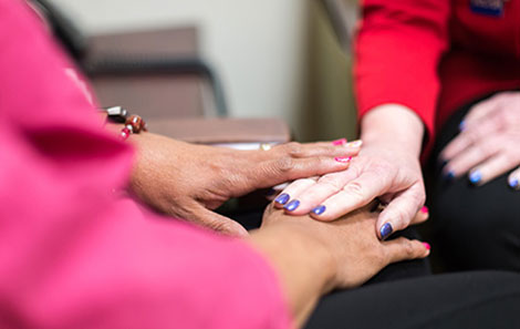 The hands of a chaplain offering spiritual support to a patient.