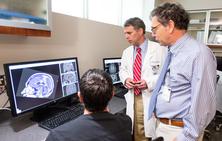 Gamma knife providers reviewing data on a computer screen.