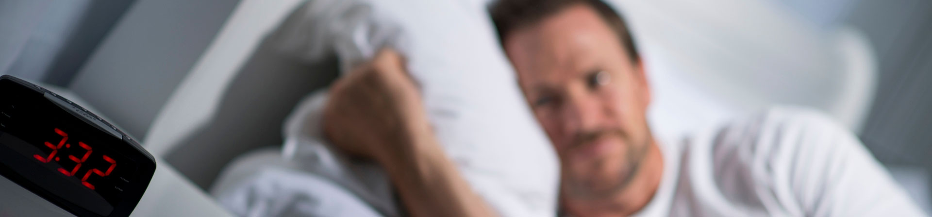 man staring at alarm clock
