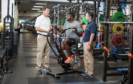 Athlete and doctors in weight room