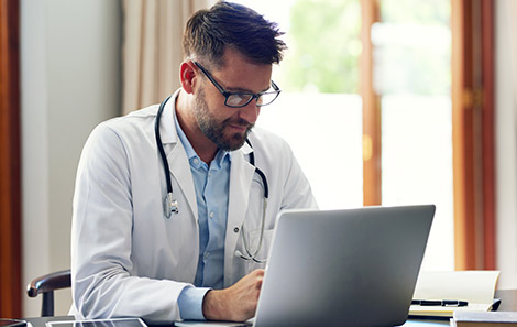 referring provider reads physician resource on his laptop