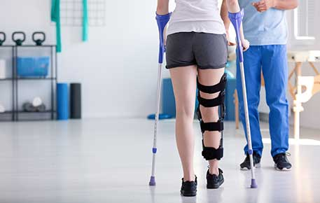 A woman learning to walk with crutches after traumatic injury getting UVA  rehab services